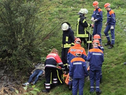 FOTO: cat Die Bergung einer ins Rückhaltebecken geschleuderten Person (links) forderte an der steilen Böschung ein halbes Dutzend Nachwuchsfeuerwehrkräfte